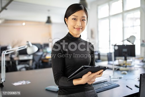 Portrait of young businesswoman standing in office with a digital tablet. Confident asian businesswoman in office.