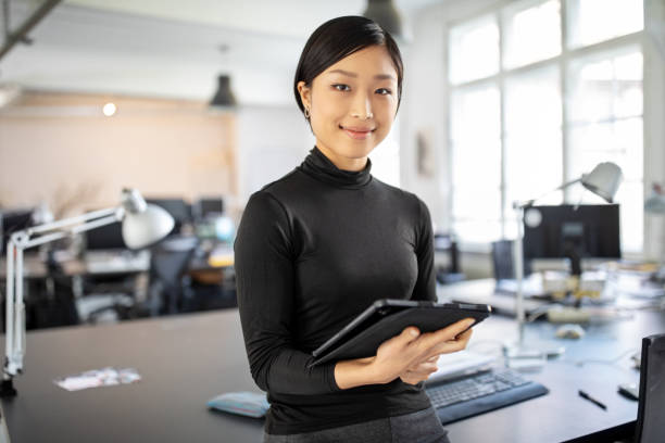 Confident asian businesswoman in office Portrait of young businesswoman standing in office with a digital tablet. Confident asian businesswoman in office. young adult stock pictures, royalty-free photos & images
