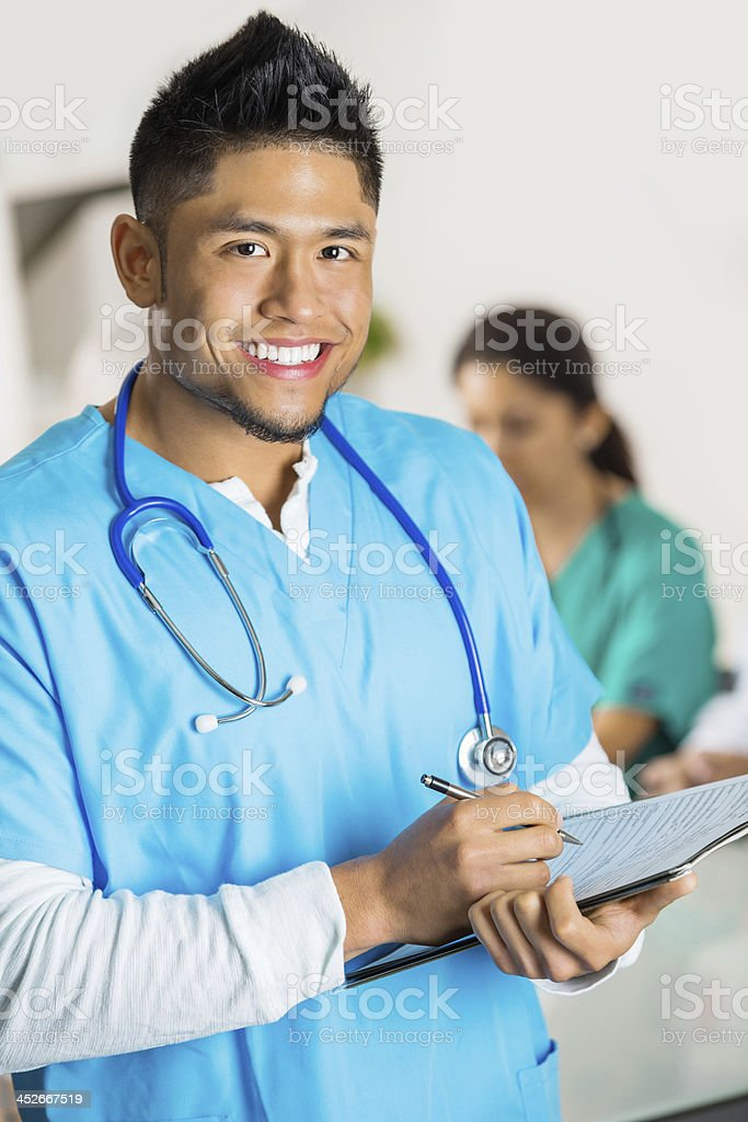 Confident Asian doctor or nurse writing in patient file stock photo