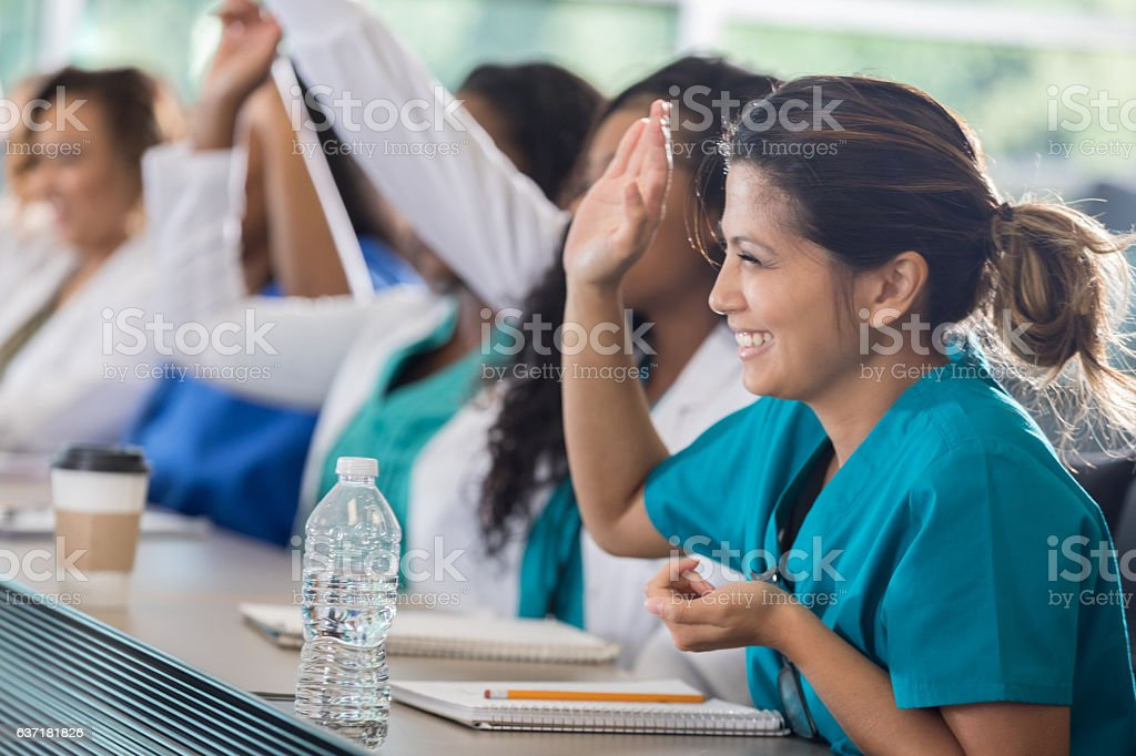 Confident Asian medical student raises hand in class stock photo
