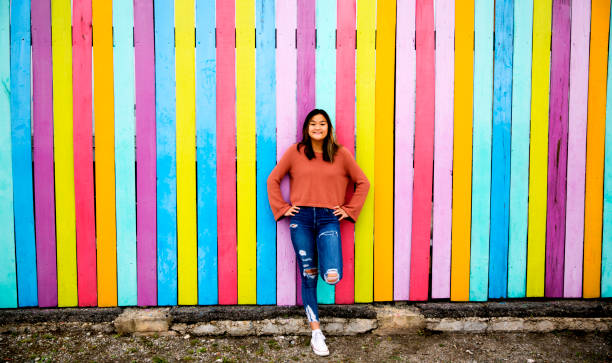 Confident Asian teen leaning against neon wall stock photo