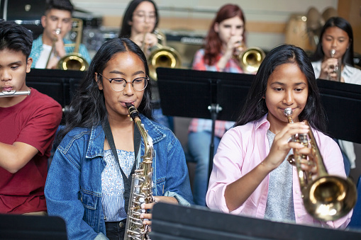Confident Asian teenage girls playing brass instruments in classroom. Students are practicing music at high school. They are learning musical instruments.