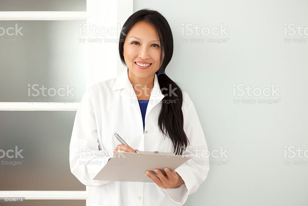 Confident Asian Woman Doctor Taking Notes On A Clipboard stock photo