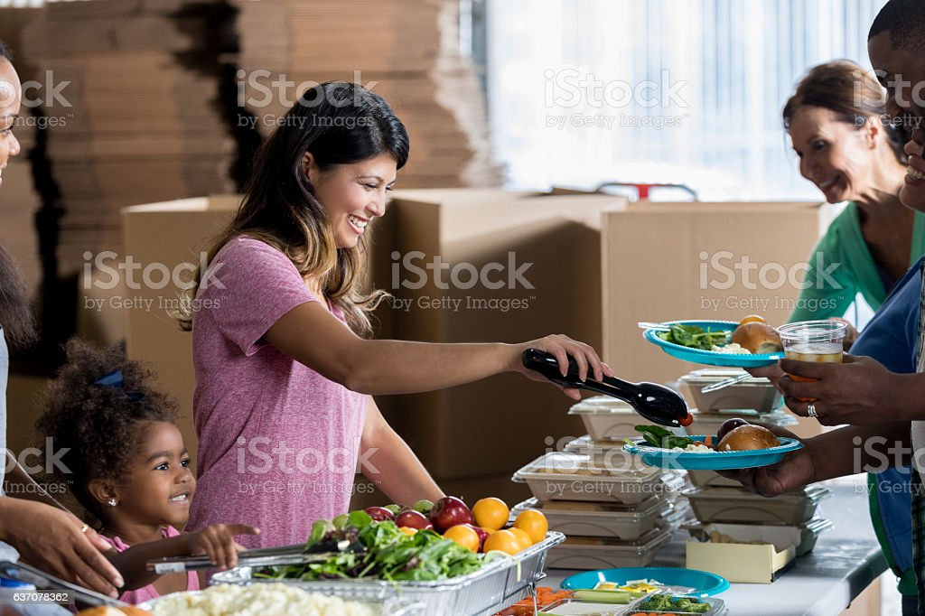 Confident Asian Woman Serves The Homeless In Soup Kitchen Royalty Free  Stock Photo