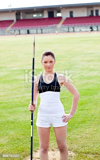 856713554istockphoto Confident athletic woman ready to throw a javelin standing in a stadium 856763332