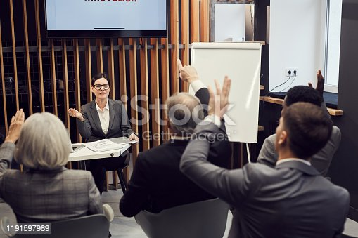 603992132 istock photo Confident attractive business lady in glasses sitting at table and answering questions of business owners participating in conference 1191597989