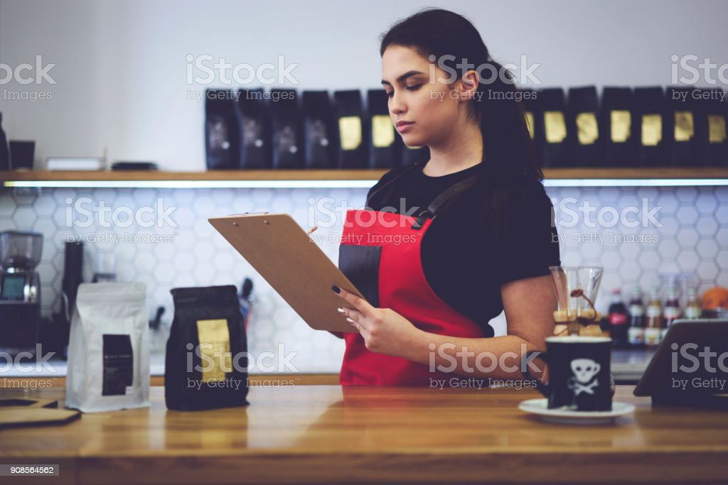 Confident attractive female administrative manager making revision checking amount of products counting monthly income working with documentation during hard working day in modern interior loft cafe stock photo