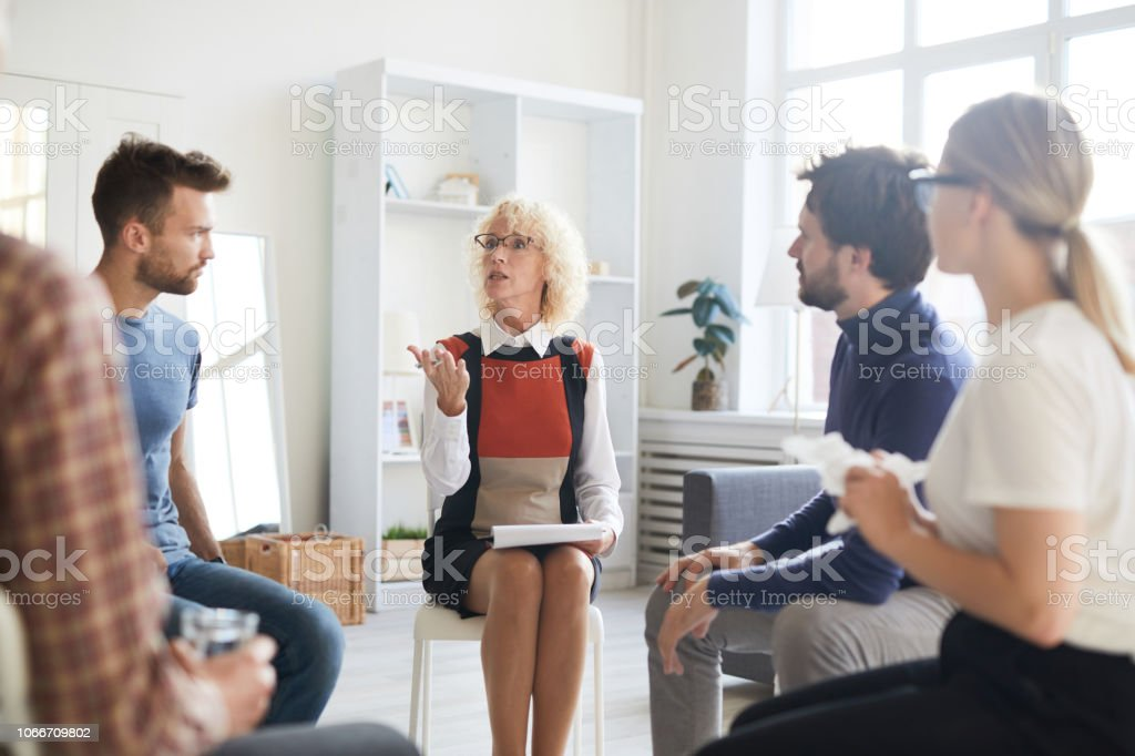 Confident attractive mature lady psychologist sitting on chair and holding clipboard while holding group therapy session with young people and teaching them to rule their emotions stock photo