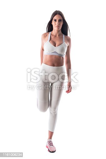 Confident attractive sporty woman in white yoga pants stretching leg muscles looking at camera. Full body isolated on white background.