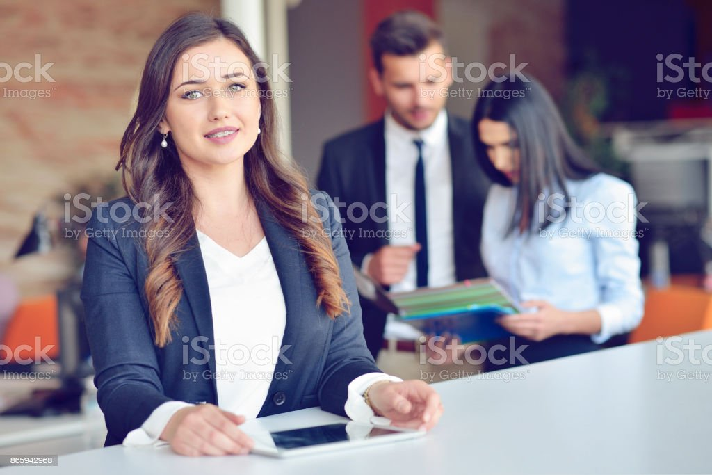 Confident attractive young business woman with tablet in hands in modern office start up office stock photo