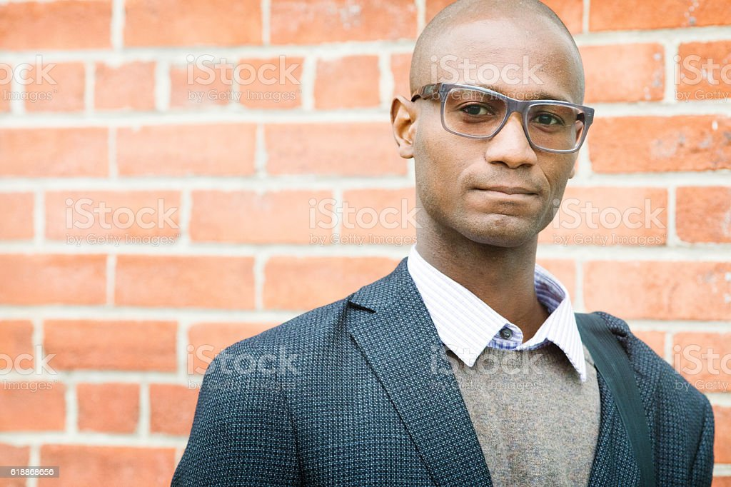 Confident bald mature black businessman portrait brick wall stock photo