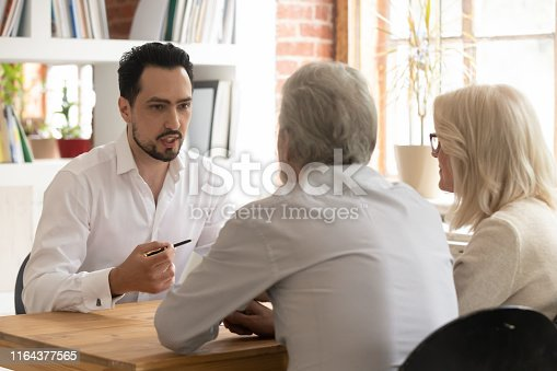 963814372istockphoto Confident bank manager consulting old senior couple clients at meeting 1164377565