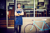 Portrait of smiling barista standing by bicycle. Confident waiter is with arms crossed outside cafe. Young male owner is wearing apron in front of the doorway.