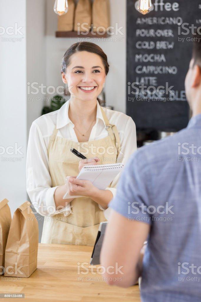Confident barista writes customer order on order pad stock photo