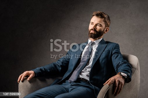 1081599130 istock photo confident bearded businessman resting in armchair 1081599090