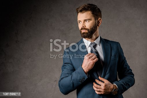 1081599130 istock photo confident bearded businessman standing in formalwear and touching tie 1081599212