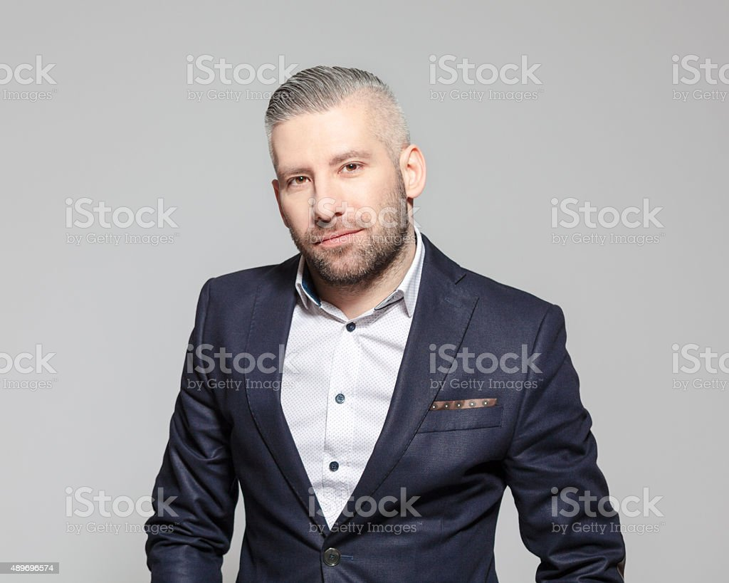 Confident bearded grey hair businessman Portrait of elegant bearded grey hair businessman standing against grey background and looking at camera. Studio shot, one person.  2015 Stock Photo
