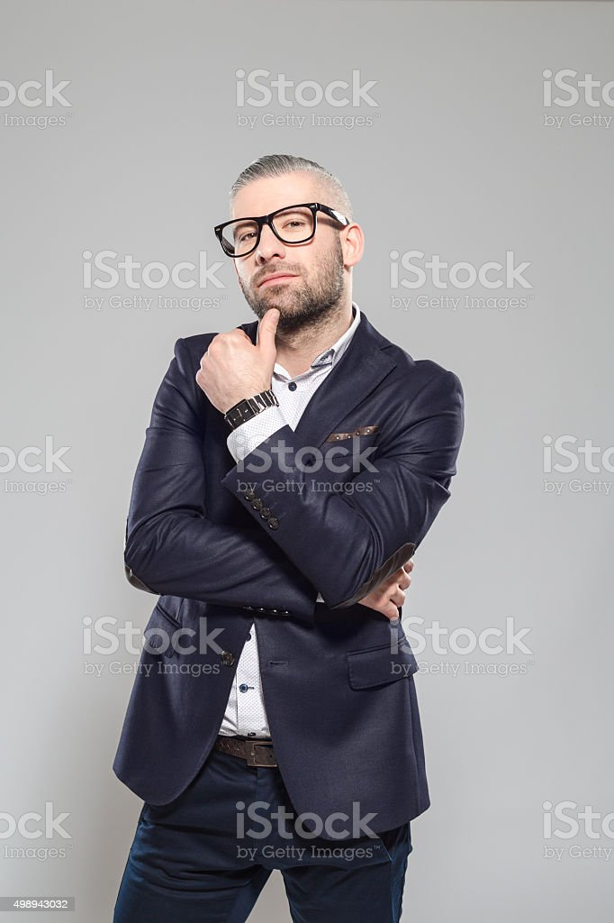 Confident bearded grey hair businessman wearing glasses Portrait of elegant bearded grey hair businessman wearing suit and nerd galsses, looking at camera with thumb on chin. Studio shot, one person, grey background. 2015 Stock Photo