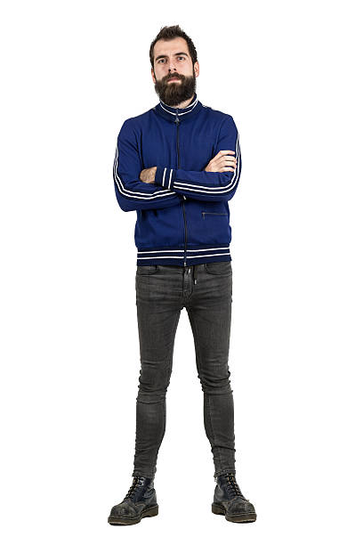 Confident bearded hipster in blue tracksuit jacket and tight jeans Confident proud bearded man in blue tracksuit jacket and tight jeans looking at camera with crossed arms. Full body length portrait isolated over white studio background. men in tight jeans stock pictures, royalty-free photos & images