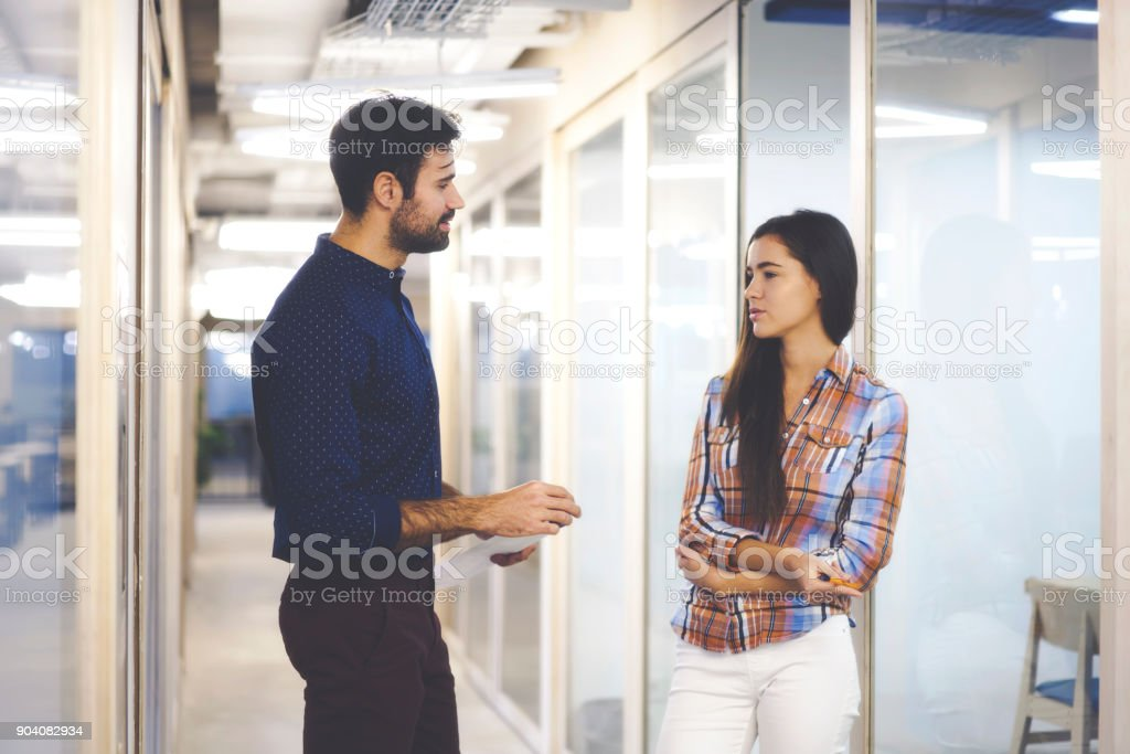 Confident bearded leader of working team consulting female trainee...