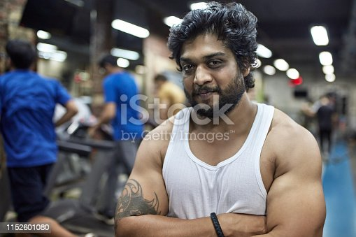 Portrait of confident muscular man with arms crossed at health club. Bearded male is in white sleeveless t-shirt. He is standing in gym.