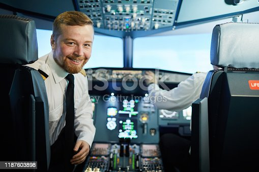 Cheerful confident bearded pilot in white shirt and black tie sitting in armchair and turning back to look at camera in cockpit