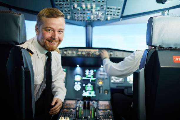 Confident bearded pilot in cockpit Cheerful confident bearded pilot in white shirt and black tie sitting in armchair and turning back to look at camera in cockpit pilot stock pictures, royalty-free photos & images
