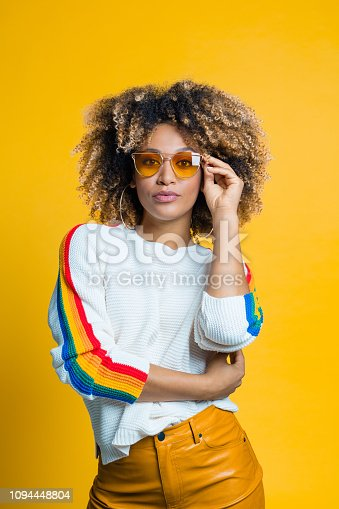 Confident afro young woman wearing blouse with rainbow pattern standing against yellow background, looking at camera. Studio shot.