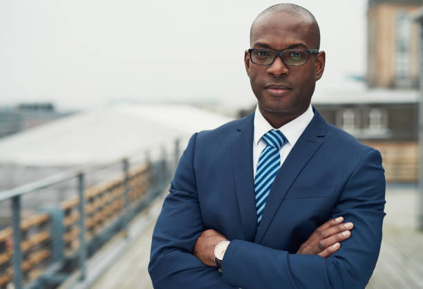 Confident black business man Confident black business man in a stylish suit standing with folded arms on a rooftop of n office block looking at the camera with a serious expression director stock pictures, royalty-free photos & images