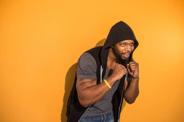 Seguros de hombre negro sobre fondo naranja boxeo - foto de stock
