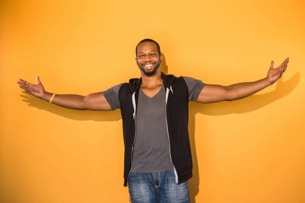 Confident Black Man on Orange Background with Arms Wide Open - foto stock