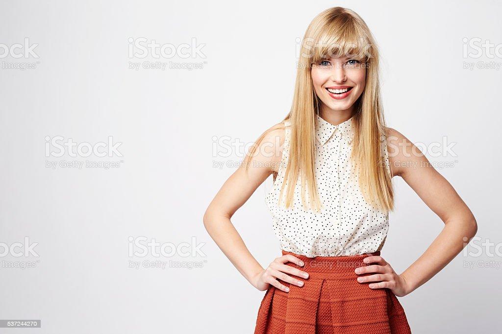 Confident blond woman in studio, portrait stock photo