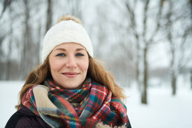 Confident blong woman sanding outside in the snow and fighting the cold with a plaid wool scarf stock photo