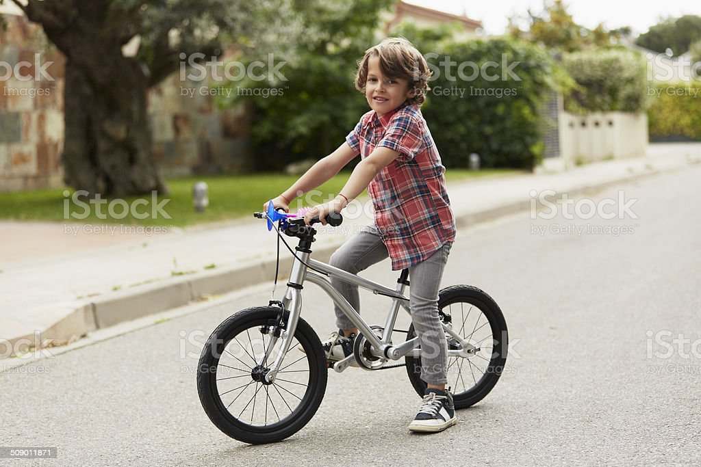Confident boy sitting on bicycle stock photo