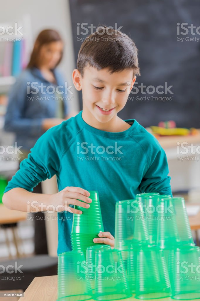 Confident boy stacks green transparent cups in classroom stock photo