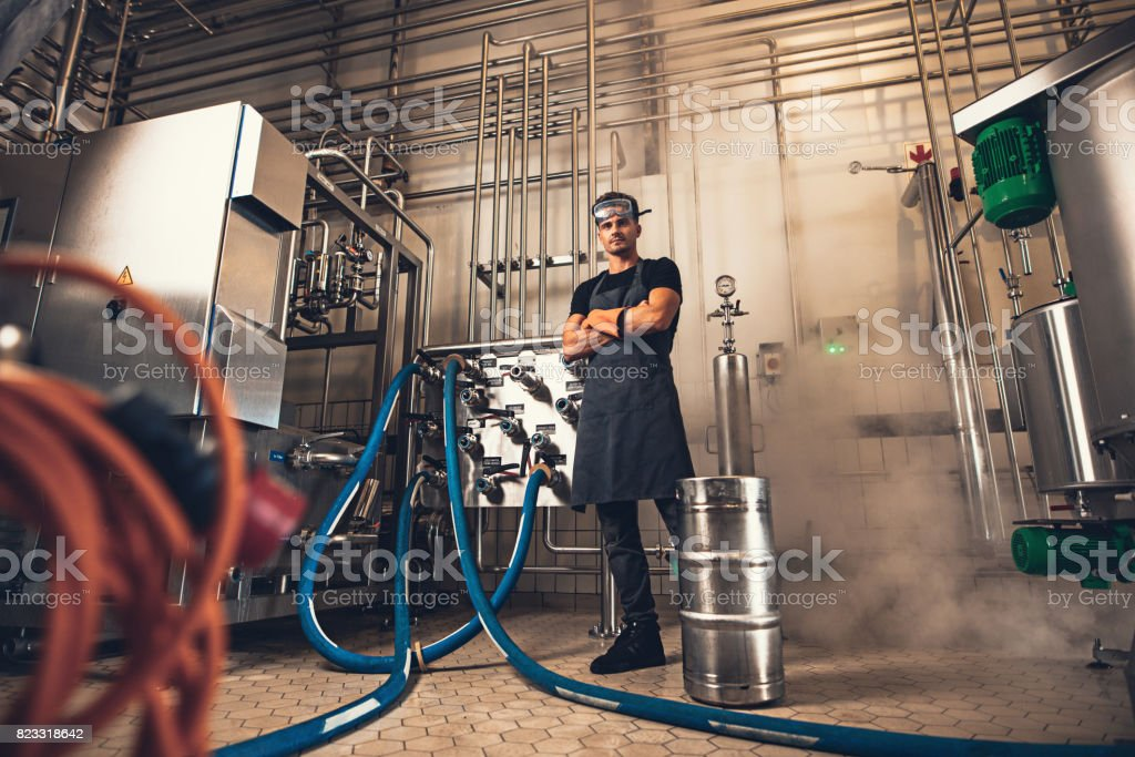 Confident brewer in apron at brewery factory - foto stock