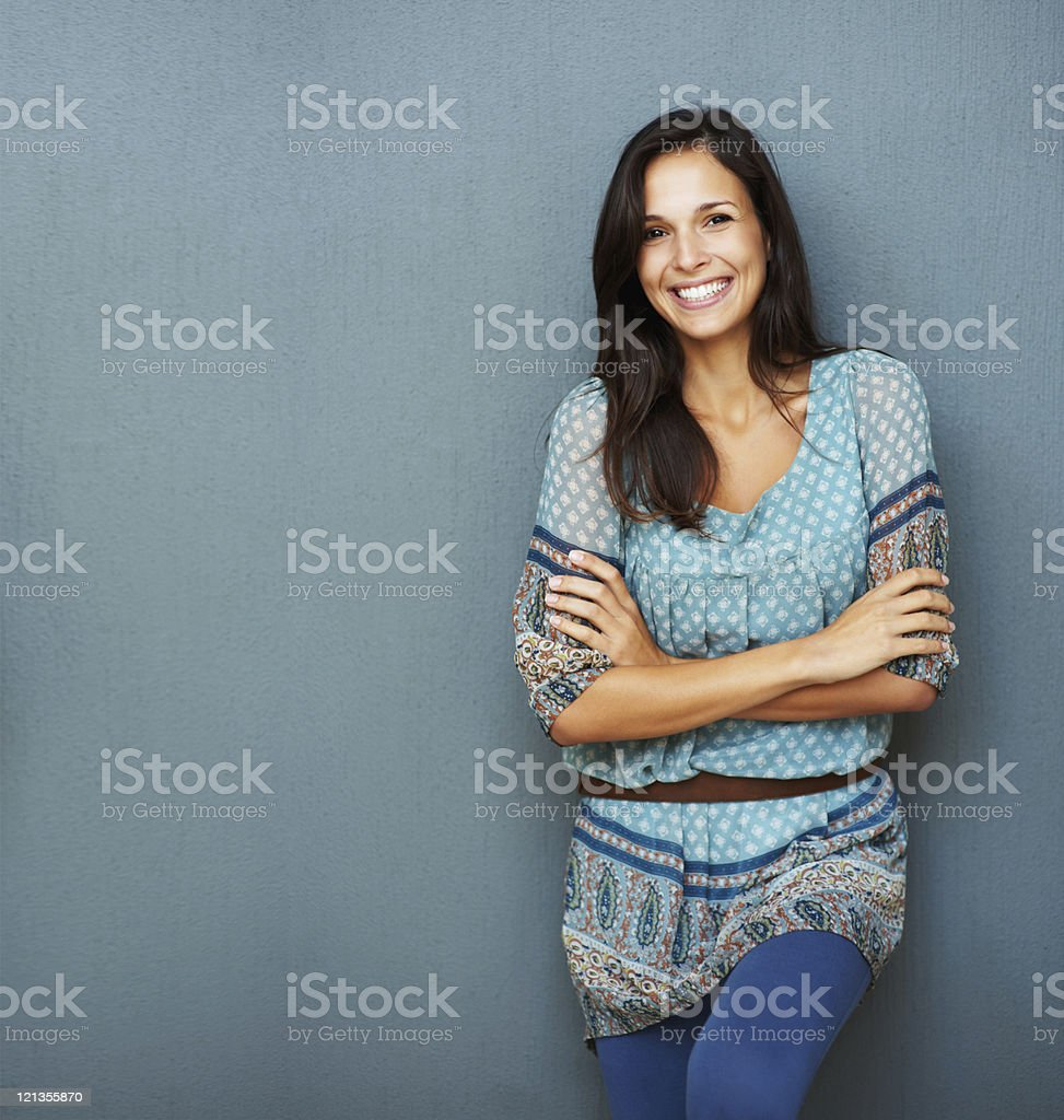 Confident brunette leans against a wall stock photo