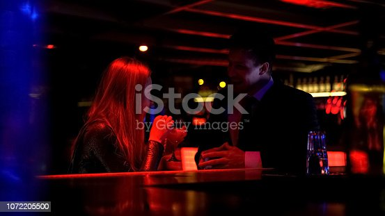 istock Confident business man talking to lady in nightclub, acquaintance, personal life 1072205500