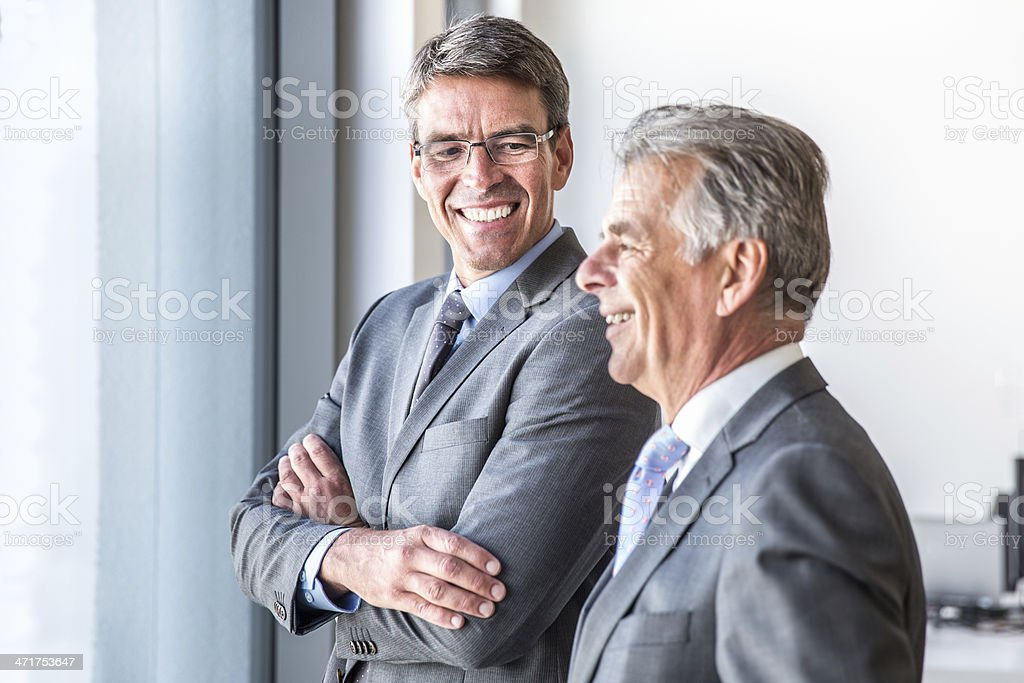 Confident Business Partners Confident business partners, managers standing together looking out the office window talking confident and happy about the closed deal. 30-39 Years Stock Photo