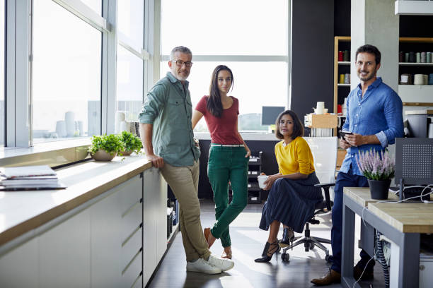 Confident business people in office Full length of confident business people in office. Male and female coworkers are in smart casuals. They are at textile industry. four people stock pictures, royalty-free photos & images