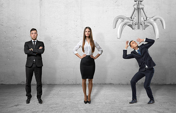 Confident business people standing straight and scared businessman shielding himself stock photo