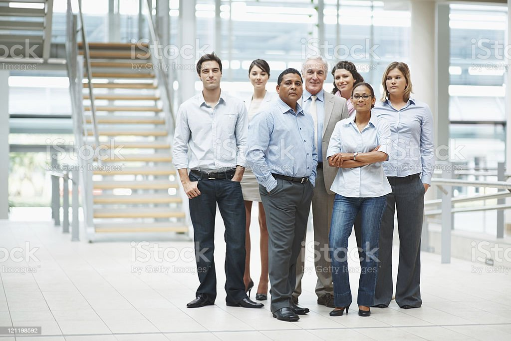 Confident business people standing together in group at office stock photo