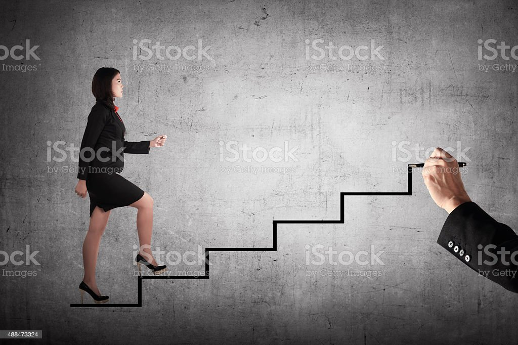 Confident business person walking upstairs stock photo