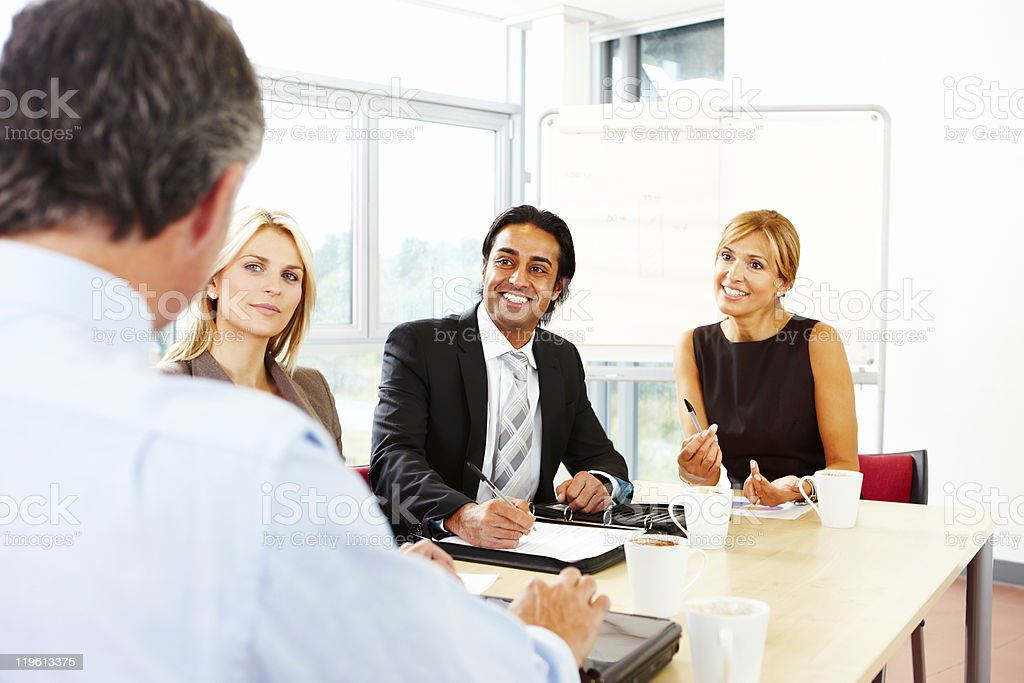 confident business team brainstorming in meeting royalty-free stock photo