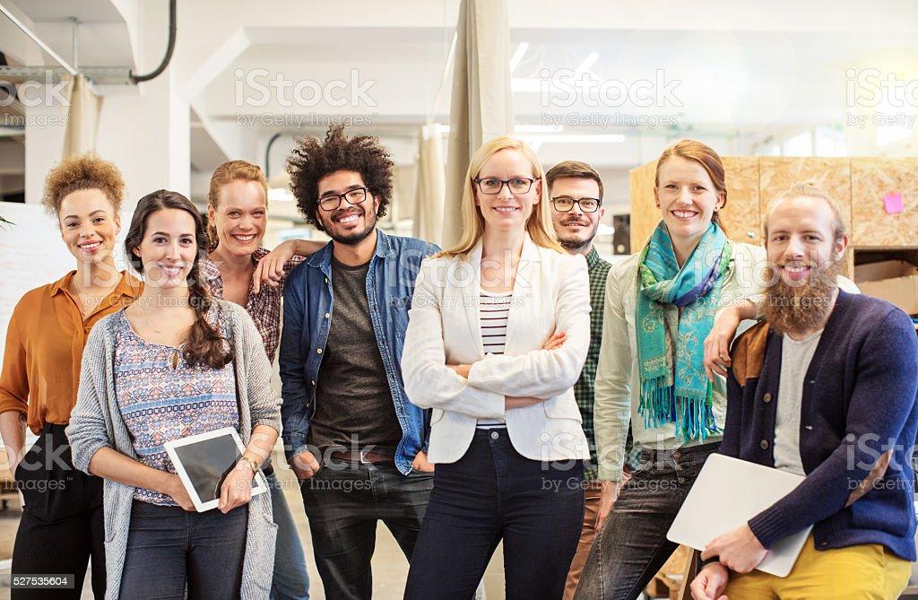 Pewnie biznes drużyna uśmiechając się w biurze – zdjęcie