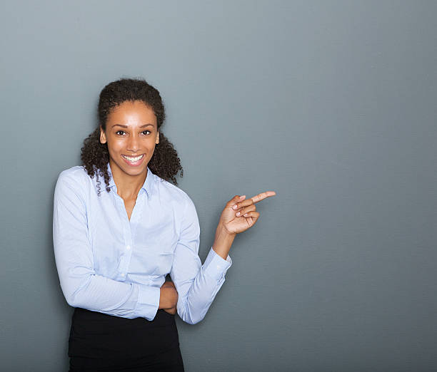 Confident business woman pointing finger stock photo