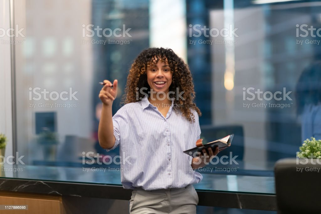 A confident black business woman stands before a window at dusk while...
