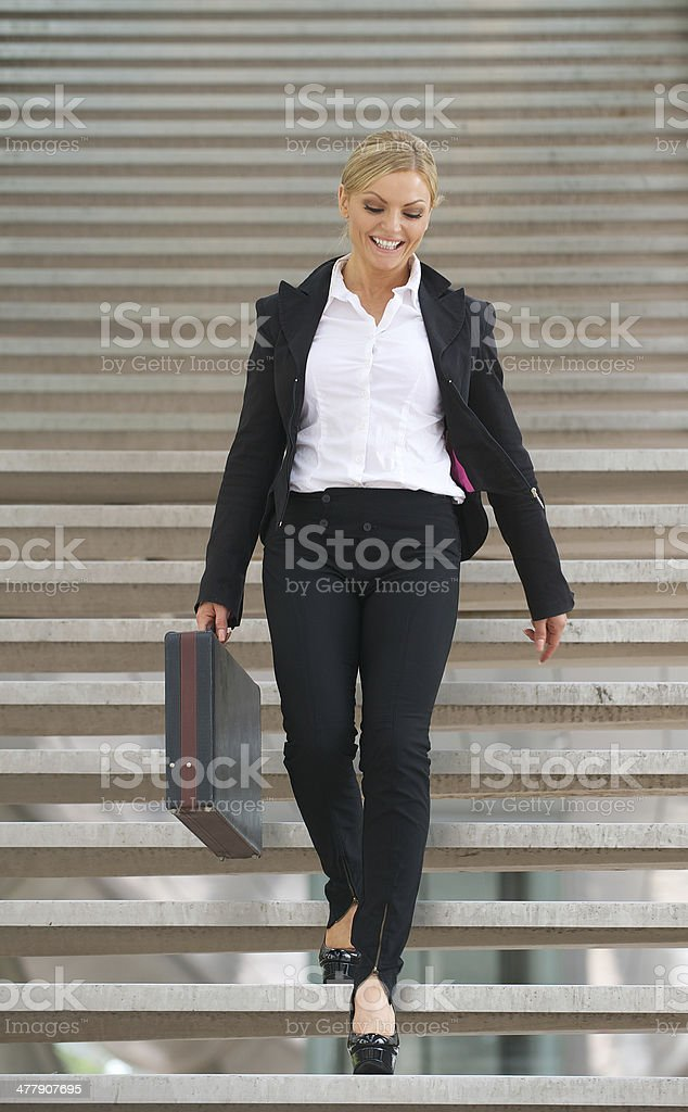 Confident business woman walking downstairs with briefcase stock photo