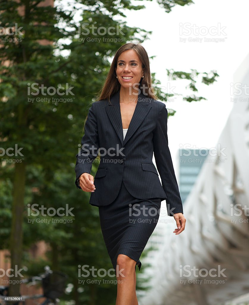 Confident business woman walking outdoors stock photo