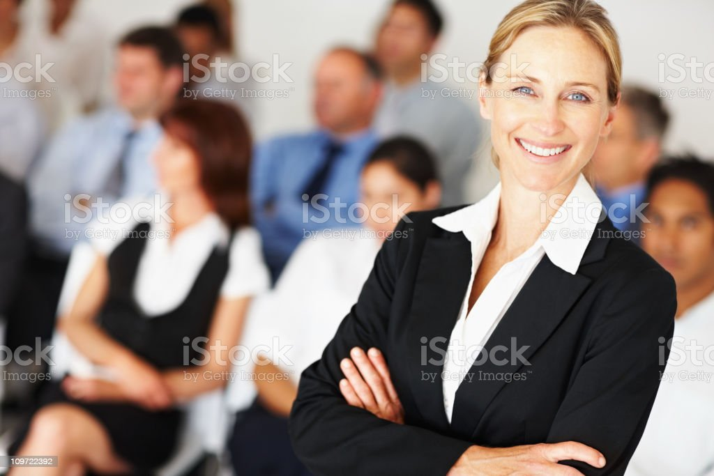 Confident business woman with colleagues at the back royalty-free stock photo